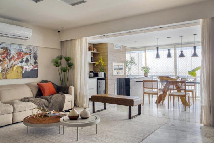 Sala de estar integrada a varanda gourmet, toda decorada em tons claros