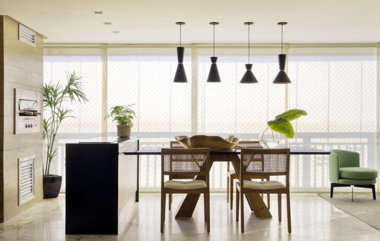 Varanda fechada com churrasqueira embutida na parede, bancada preta alta em frente e uma mesa de madeira ao lado na perpendicular