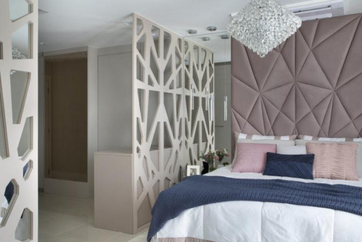 Quarto de casal decorado em tons suaves, cabeceira estofada até o teto com placas em formatos geométricos, cama com colcha branca e almofadas rosa, painel vazado separando a cama  do closet