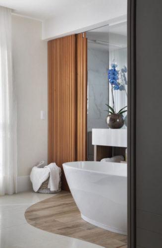Banheiro aberto pra o quato com uma banheira branca oval no meio.