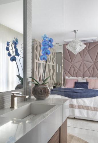 Banheiro incorporado ao quarto, cama de casal ao fundo e na frete cuba esculpida na bancada bege