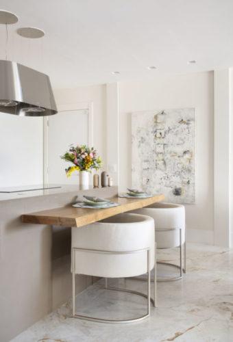 Bancada de madeira mais baixa que a bancada do cooktop, com cadeiras brancas com encosto almofado e circular