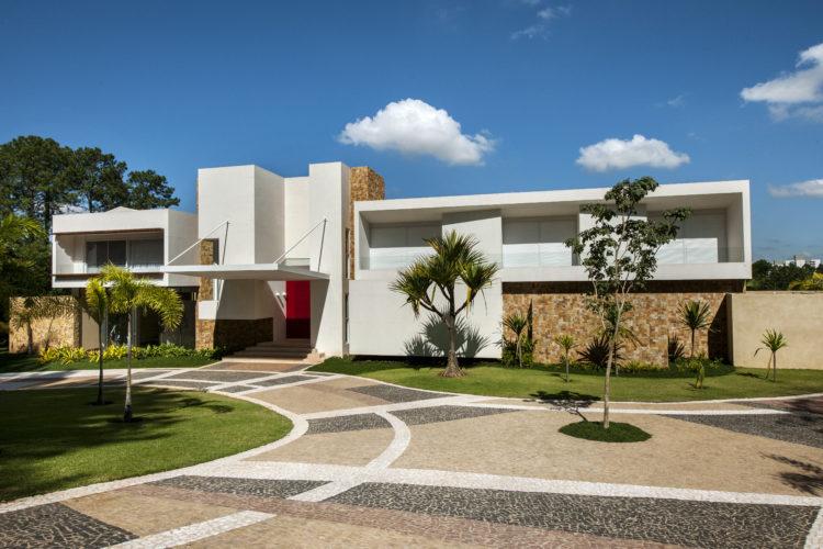 Último projeto residencial do arquiteto e urbanista Noel Marinho em Jundiaí, interior de São Paulo. Casa com estilo arquitetônico modernista, fachada branca com muros de pedra. Volumetria em quadrados e retângulos brancos