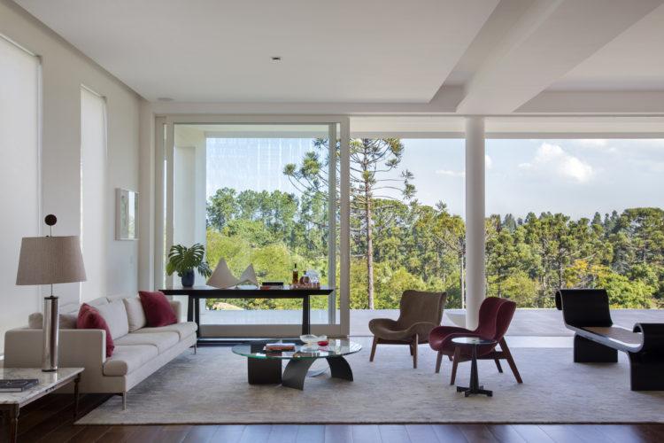 Sala ampla totalmente integrada a vista do do verde do lado de fora, por grandes painéis de vidro