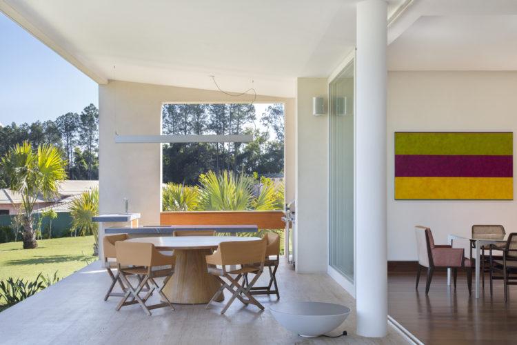 Mesa redonda na varanda aberta para o jardim.