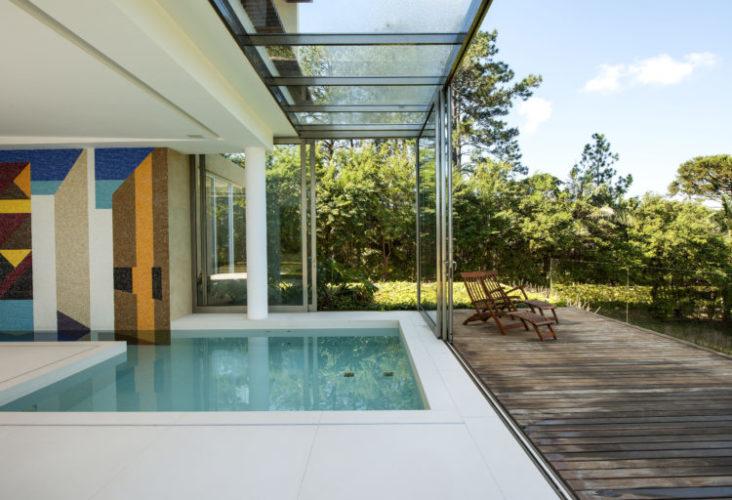 Varanda com deck em madeira, atrás, piscina coberta mas integrada por grandes portas de correr em vidro, e na parede fundo da piscina um painel de azulejos de Noel Marinho.
