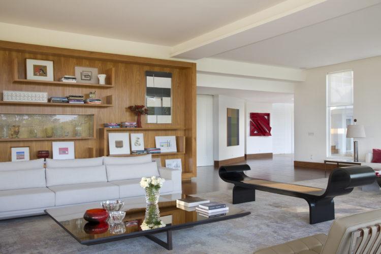 Ampla sala com sofá branco, atrás uma parede revestida de madeira e alguns nichos, formando uma estante. Ao lado o móvel marquesa de Oscar N