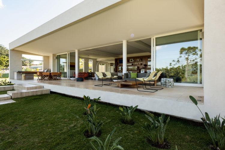 Varanda da casa em formato de um bloco retangular, com grandes painéis de vidros e portas de correr.
