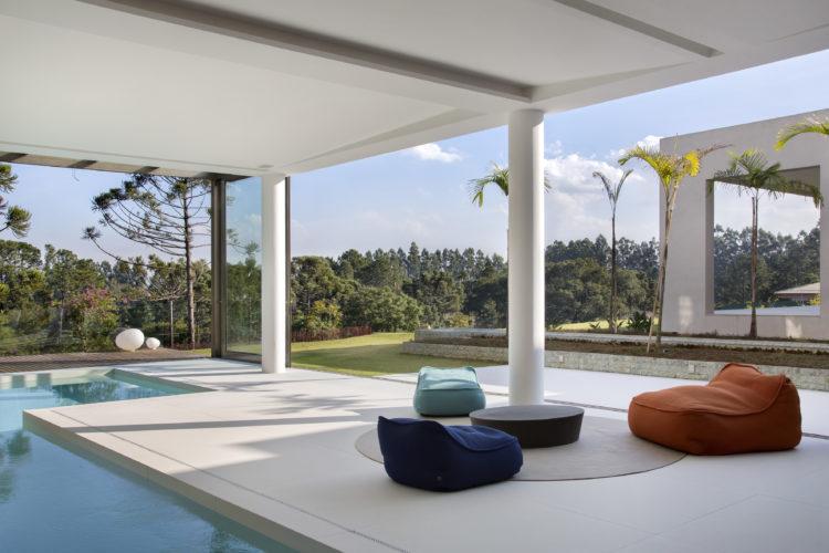 Varanda aberta, integrada ao exterior, colunas, piscina coberta e mobiliário contemporâneo composto por três poltronas baixas e coloridas.