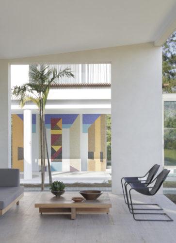 Sala com grande painel em vidro, e no fundo, vista para o painel de pastilha de vidro de Noel Marinho.