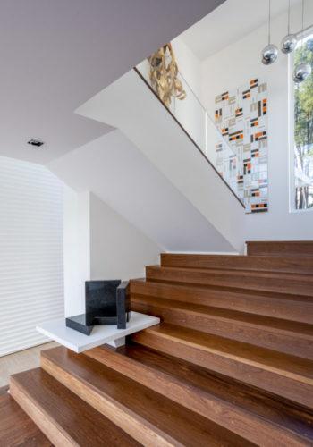 Escada em madeira com uma prateleira branca no meio que abriga uma obra de arte de Amilcar de Castro, no patamar, um painel de azulejos de Noel Marinho.