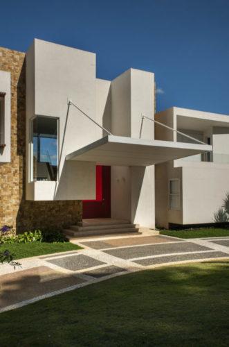 Último projeto residencial do arquiteto e urbanista Noel Marinho. Entrada da casa, volume branco em forma de retângulo na vertical, porta de entrada vermelha e um marquise quadrada em balanço.