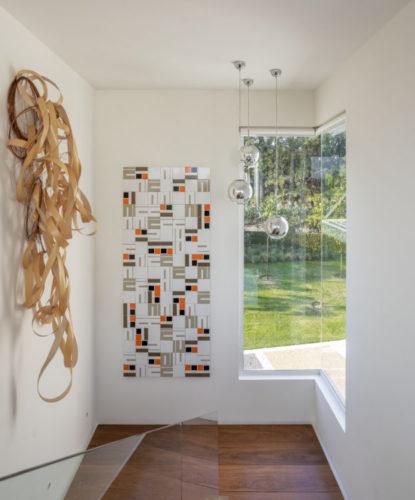 """O painel de azulejos da série CORBU, matriz criada por Noel Marinho a partir de uma pintura sobre tela de 2012, mede 1,09m de largura x 2,64m de altura e foi criado sob medida para o local, em harmonia com a escultura de Frida Baranek"""", no patamar da escada de um casa em Jundiai, no interior de Sp."""