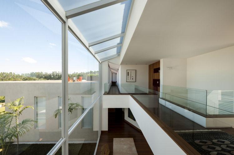 Parte interna da casa, segundo andar com piso em madeira e guarda corpo em vidro.