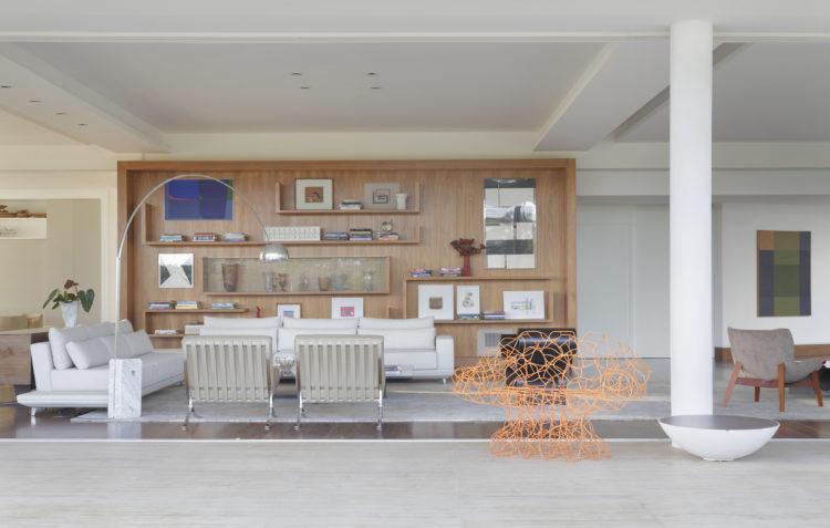 Sala em uma casa projetada por Noel Marinho em São Paulo. Ampla, integrada a varada por porta de correr em vidro. Parede de fundo revestida em madeira e sofá branco na frente.