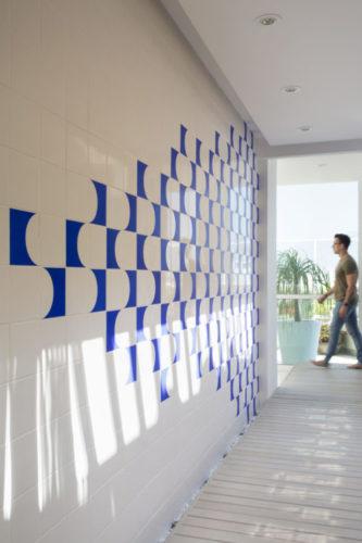 área de circulação de um segundo andar da cobertura, corredor com uma parede lateral revestida com um painel de azulejos na cor azul e branca.