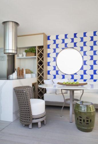 Varanda fechada com espaço gourmet, coifa, churrasqueira e cooktop na bancada. Ao lado mesa com sofá e na parede atrás um painel em azulejos branco e azuis