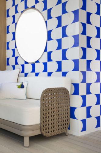 Parede em destaque com azulejos na cor azul e branco formando um painel.