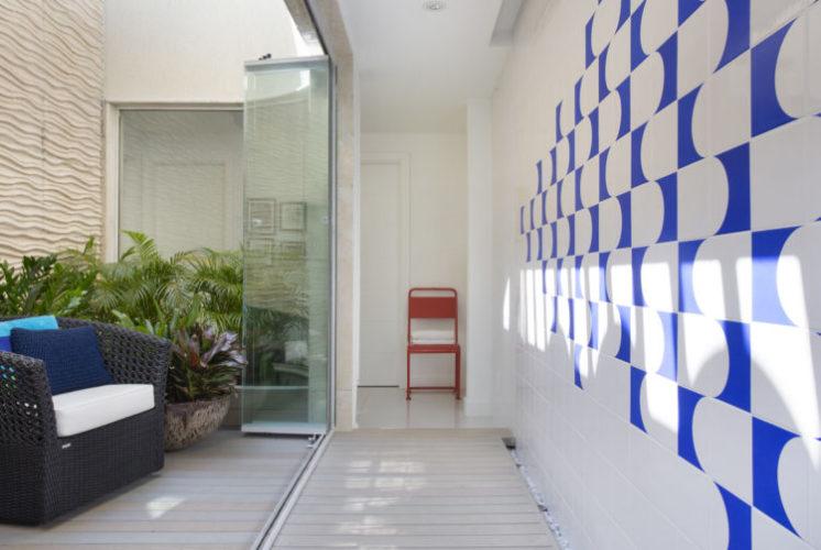 Circulação do segundo andar da cobertura, parede revestida com painel de azulejos na cor azul e branco.