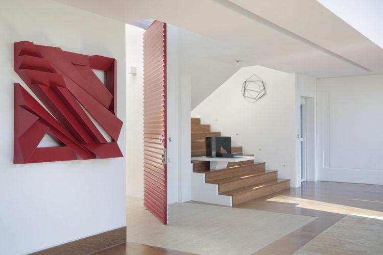 Hall de entrada de uma cada em Jundiaí,. Grande, claro, pintado de branco, porta de entrada ripada e pintada de vermelho, uma escultura vermelha na parede ao lado. E no outro , uma escada em madeira