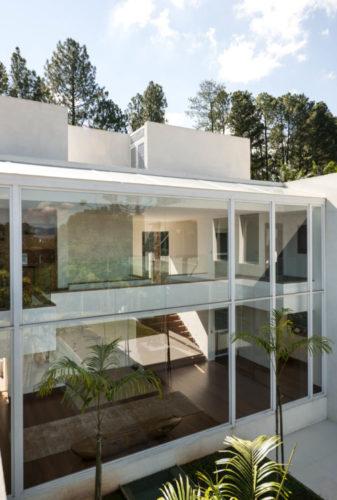 Fachada de vidro, virada para um pátio interno de uma casa em Jundiaí, interior de SP.