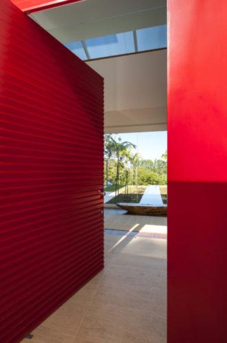 Porta de entrada e portal em vermelho abrindo para um jardim.