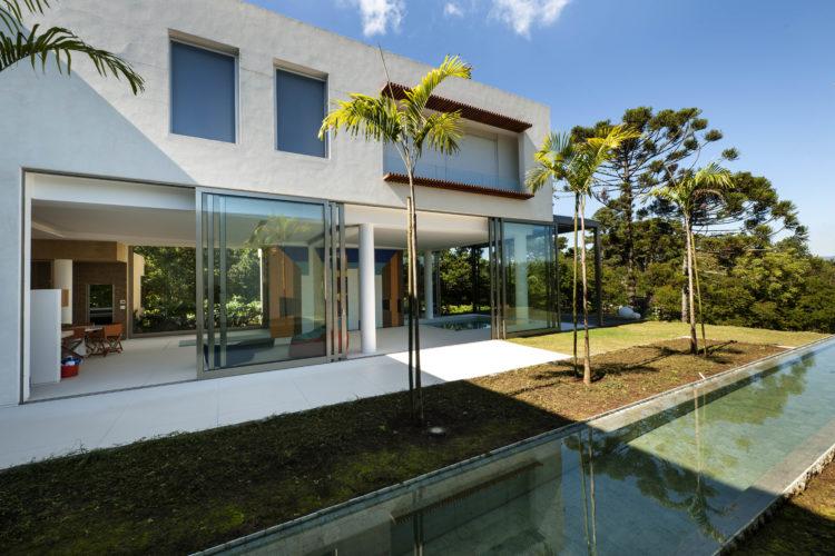 Casa com fachada branca, grandes portas de correr em frete a um jardim com raia de piscina e palmeiras