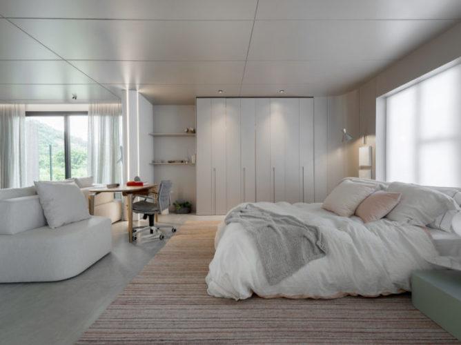 Quarto amplo e claro no espaço de uma mostra de decoração, cama branca, armário e sofá branco