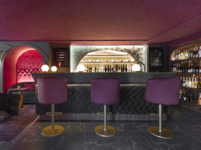 CASACOR Santa Catarina 2021. Clima de bar, com ambiente mais escuro, bar com poltronas altas na cor roxo