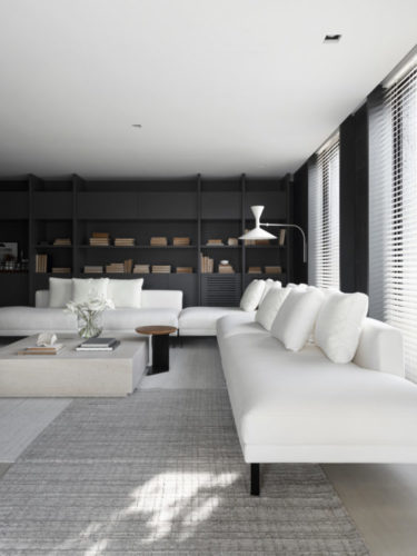 Ambiente decorado, sofá branco e grande em L , ao fundo, estante preta.