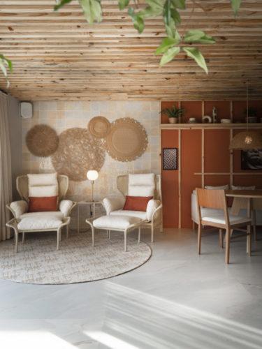 Ambiente claro, teto em bambu e duas poltronas de vime na parede atrás um conjunto de cestas