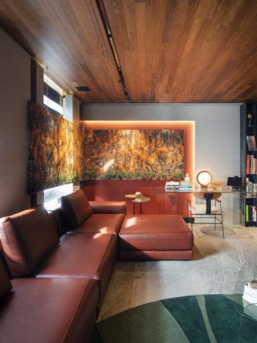 Sofá em couro marrom com chaise, na parede lateral, um nicho iluminado e pintado de laranja abriga um quadro.