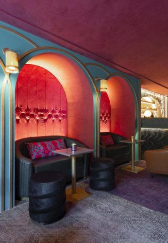 Ambiente com nichos em arco, parede vermelha de fundo, mini sofá e mesinha na frente, clima de bar