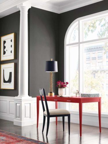 Tendências de cores de tinta para 2022, previsão anual da Colormix da Sherwin-William. Parede pintada de cinza escuro, rodapé bem alto em branco. Em frente a uma grande janela, uma escrivaninha vermelha