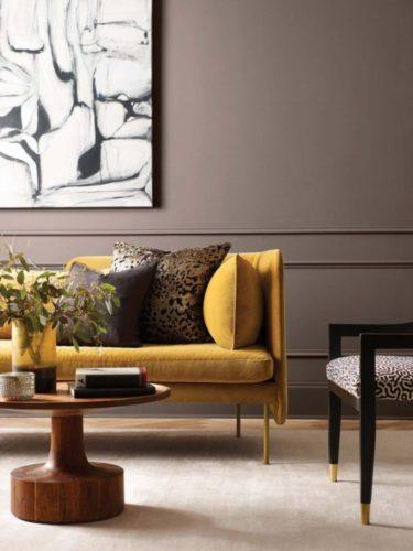 Decoração em tons neutros. Parede em cinza com aplicação de boiserie também pintada, em frente, sofá amarelo em veludo com almofadas em estampa de onça.