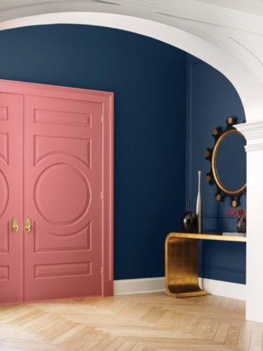 Tendências de cores de tinta para 2022, previsão anual da Colormix da Sherwin-William. Hall de entrada com a parede pintada de azul, porta de entrada rosa e uma aparador dourado