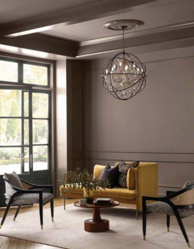 Sala com decoração contemporânea. Parede e teto pintado na cor cinza escuro, sofá amarelo em veludo
