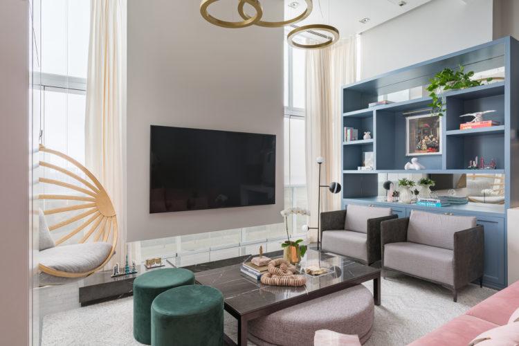 Sofá rosa como ponto de partida para o décor. Sala ampla, pé direto alto. Estante azul e em frente duas poltronas na cor cinza.. TV na parede em frente a janela.