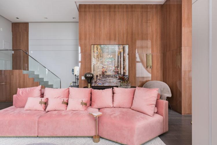 Decoração chic e contemporânea, sofá curvo na cor rosa no centro da sala. Ao fundo parede revestida em painel de madeira brilhoso