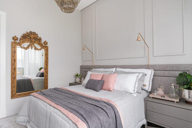 Quarto com decoração clássica. Nas cores cinza, roda e branco e um espelho dourado na parede lateral da cama