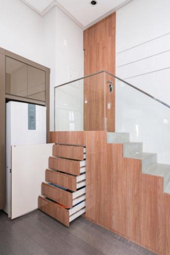 Escada de acesso ao apartamento, ao lado da cozinha, com a parte mais alta cheio de gavetas.
