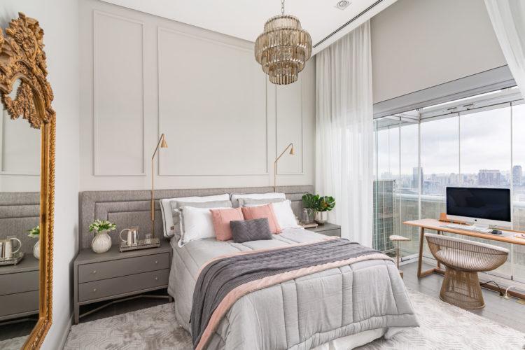 Quarto com decoração clássica. Boiserie atrás da cama, ao lado na parede, um espelho com moldura dourada