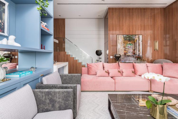 Sofá rosa como ponto de partida para o décor. Sala apla e clara, ao fundo , parede revestida em madeira. Sofá rosa, ao lado estante pintada de azul
