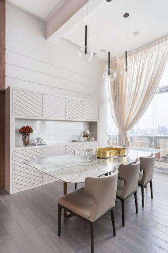 Sala de jantar com a decração toda clara. mesa em marmore a um aparador em laca branca com nicho e portas superiores e inferiores.