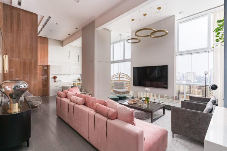 Sala com pé direito alto, janelas grandes, ambiente claro. Tv de costas para a janela, em frente , um sofá rosa