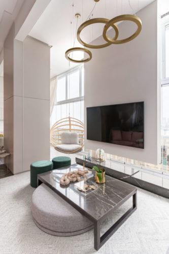 Sala ampla e clara. No teto, luminária pendente em forma de círculos. Um painel em frente a janela abriga a Tv. Mesinha de centro em pedra e na lateral, um balanço redondo suspenso.