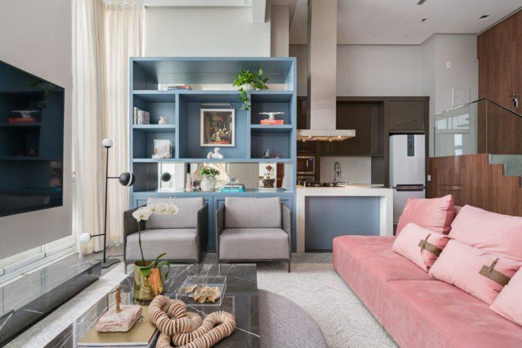Sala com cozinha aberta. Estante azul, ao lado a cozinha aberta. Sofá grande rosa no centro da sala