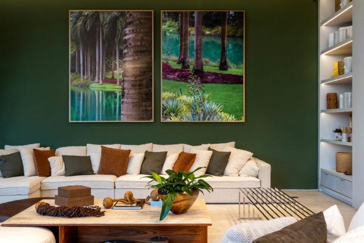 Interior da loja Breton, decorada por Bia Elias e Maria Fernanda. Parede pintada de verde floresta, dois retratos na natureza no meio da parede , em cima do sofá branco com almofadas lidas em verde e na cor tijolo