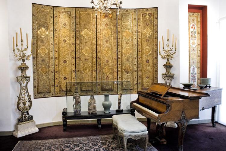 Casa Museu Ema Klabin reabre em São Paulo. Sala de musica com piano, tapeçaria na parede e ao lado, esculturas em madeira
