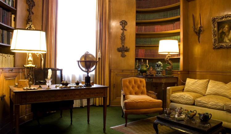 Casa Museu Ema Klabin, biblioteca. Paredes forradas em madeira com estantes para os livros. Ambiente acolhedor, com sofá, escrivaninha e iluminação feita por abajures.